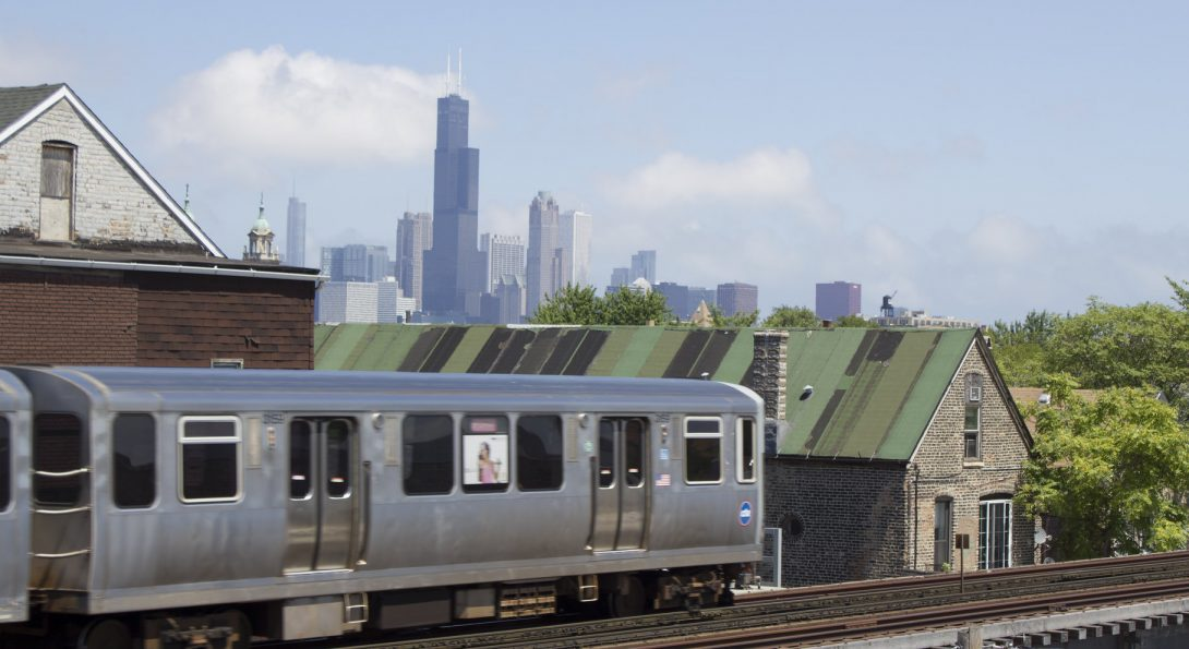 Image of red line train with the skyline in the background